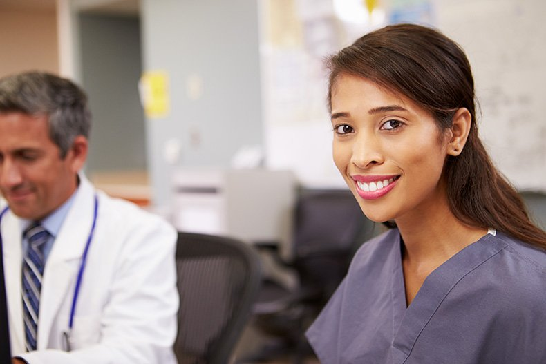 Asian nurse smiling with doctor in the background