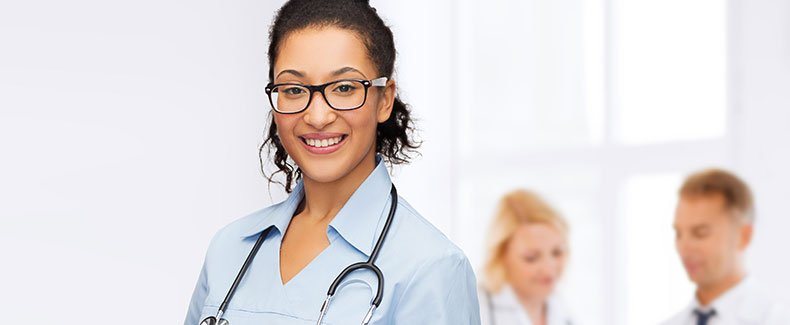 Smiling female nurse with man and woman in background