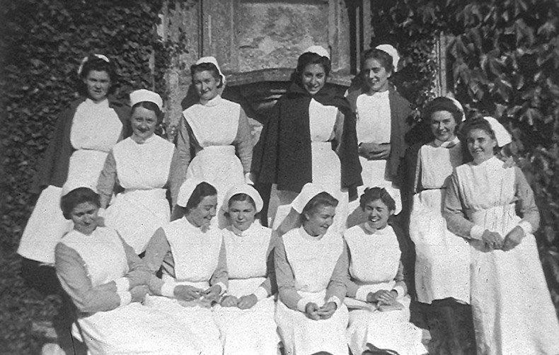 Old photo of happy nurses outside hospital
